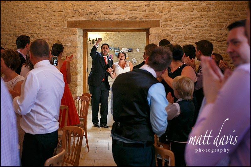 Couple enter their wedding breakfast during a summer wedding at Kingscote Barn