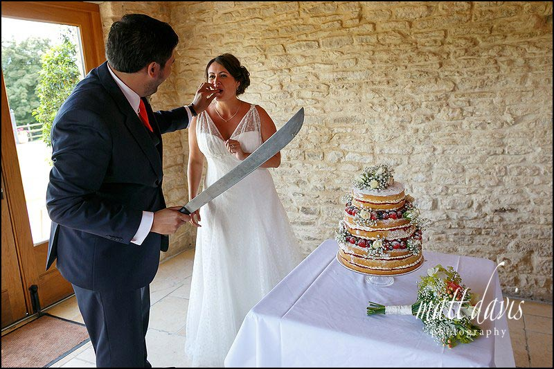 Cutting the cake during a summer wedding at Kingscote Barn