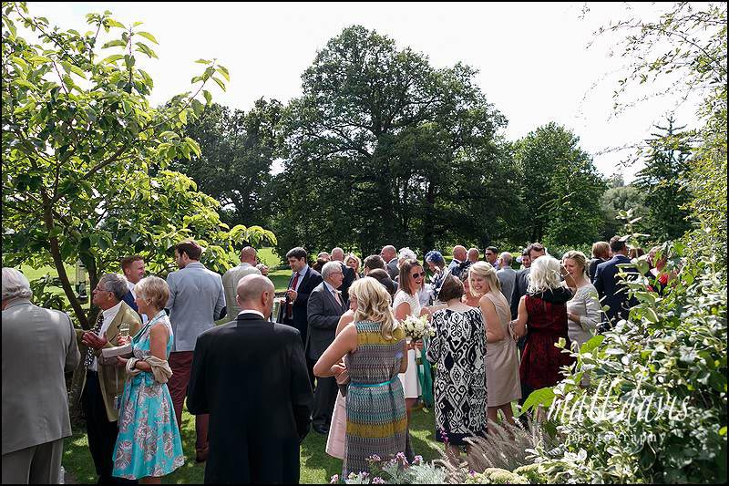 Wedding guests at Birtsmorton Court drinking on the gun terrace