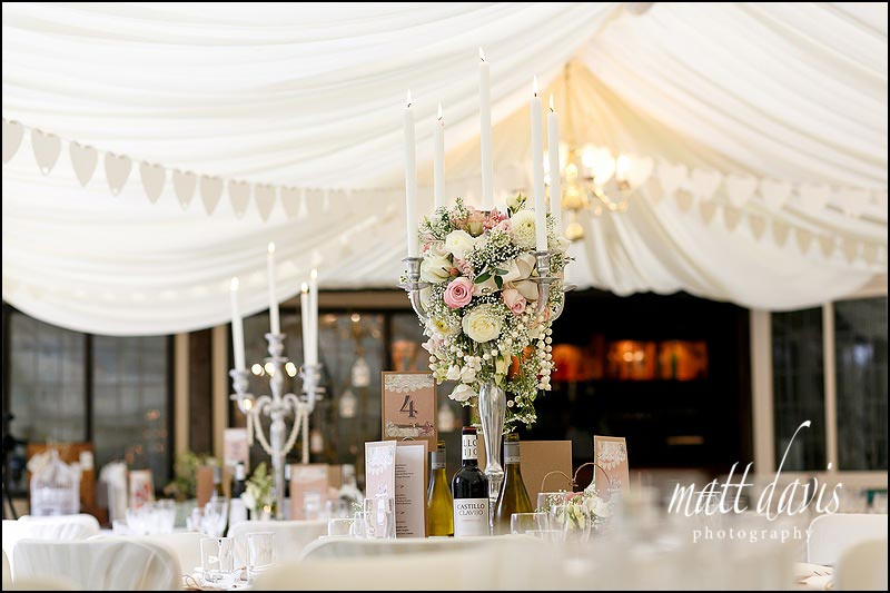 Candle arbors with flower details inside the marquee at Birtsmorton Court
