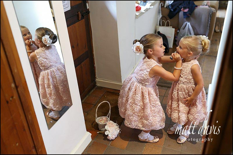 Flower girls applying lipstick.  Documentary wedding photography by Matt Davis Photography.