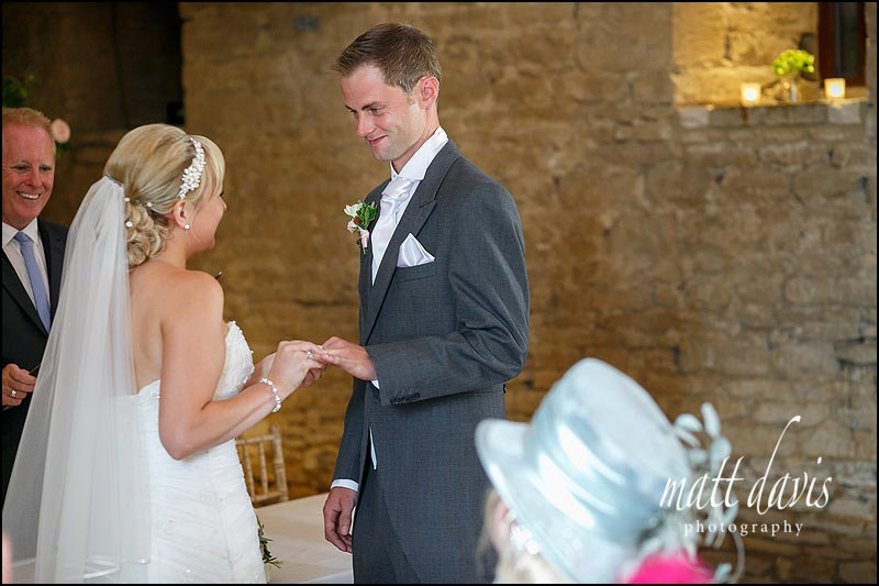 Married couple exchange rings at the Great Tythe Barn, Tetbury, Gloucestershire