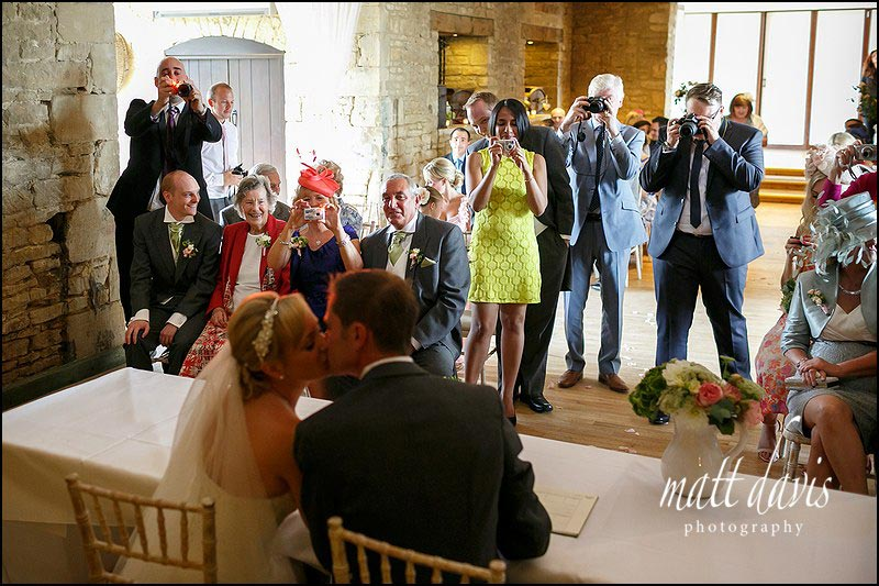 Great Tythe Barn wedding photos showing couple kissing in front of wedding guests