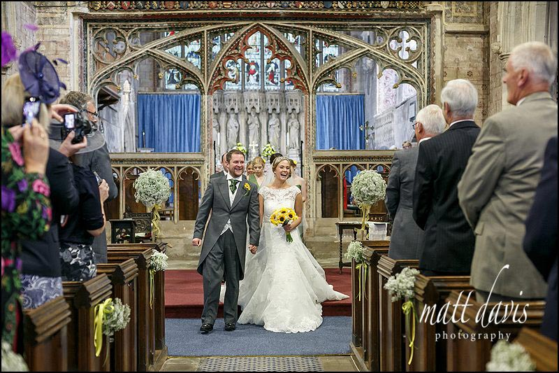 wedding couple walking down the aisle at St Mary's church, Berkeley, Gloucestershire