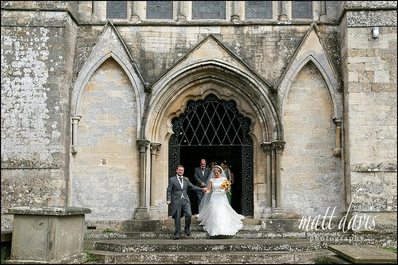 Wedding couple outside St Mary's church, Berkeley, Gloucestershire