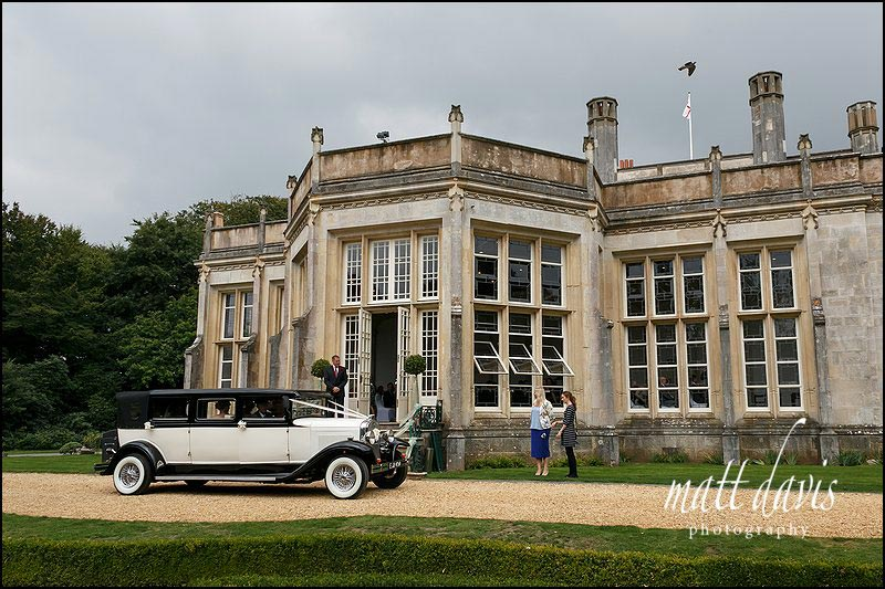 Brides arrival at Highcliffe castle in a vintage car for a wedding