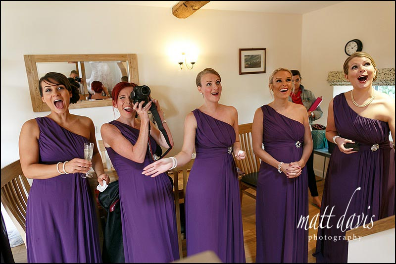 Fun wedding at Kingscote Barn with bridesmaid cheering as bride enter the room