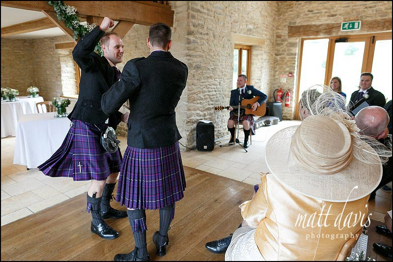 Groom dancing before the wedding ceremony during a fun wedding at Kingscote Barn