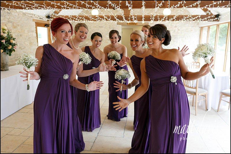 Fun wedding at Kingscote Barn with bridesmaids in purple full length dresses