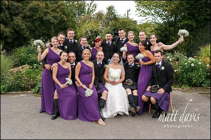 Fun wedding photos at Kingscote Barn with mixed group photo of bridal party