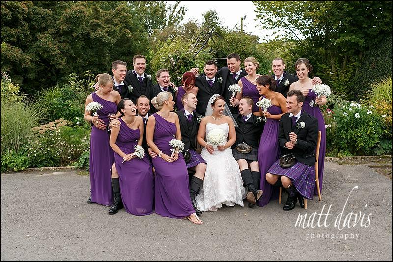 Fun wedding at Kingscote Barn with mixed group photo of bridal party