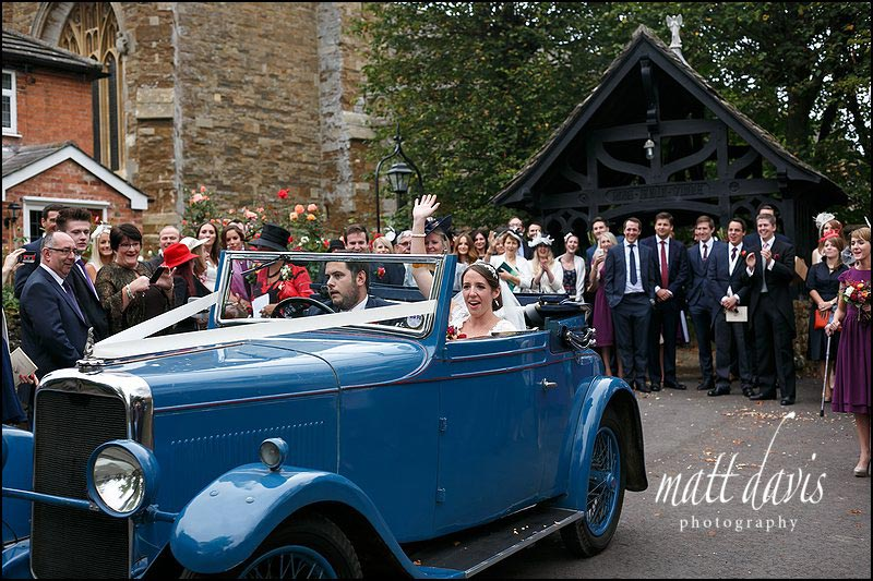 Vintage adding car leaving a quintessentially English wedding in Oxfordshire