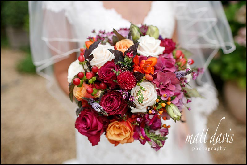 Autumnal wedding bouquet with reds, dusky pinks and orange flowers & berries.