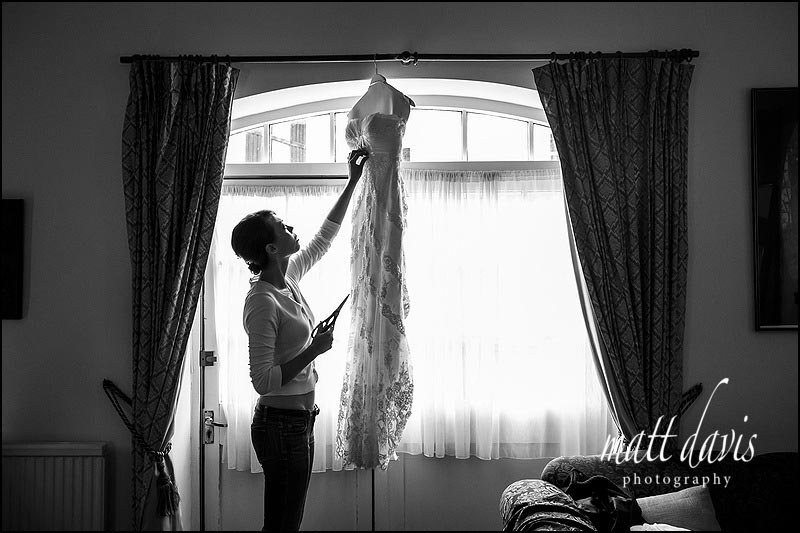 bridesmaid cutting labels out of wedding dress