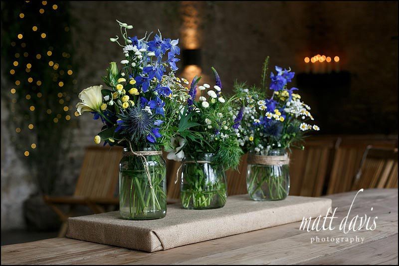 Bright flowers in jam jars for wedding decorations