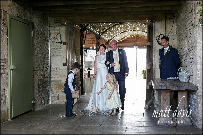 Flower girl and paige boy scatter petals at Cripps Stone Barn