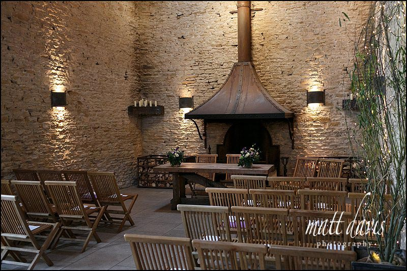 Inside Cripps Stone Barn with the wedding ceremony set in front of the main fire