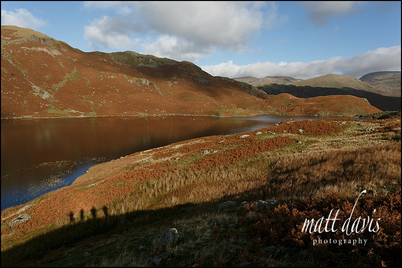 Easedale Tarn and four walkers in the shadows