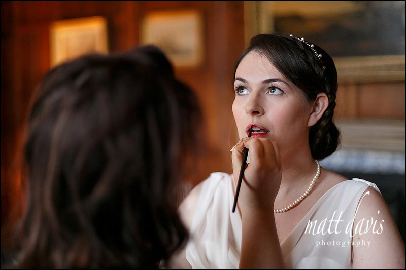 Bride with dark hair and bright red lipstick styled for winter wedding at Elmore Court