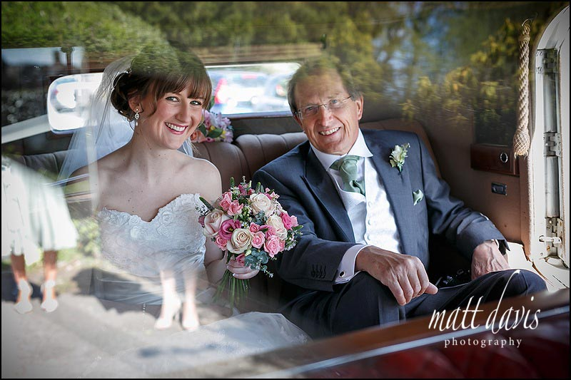 Wedding photography of bride and father arriving at church in wedding car