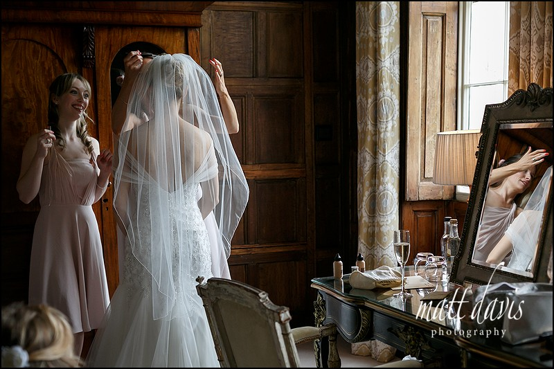 Wedding photography at Elmore Court with bride putting veil in.