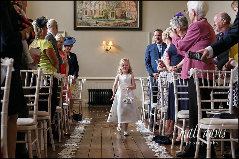 Flower girl dropping petals along the aisle at Elmore Court civil ceremony