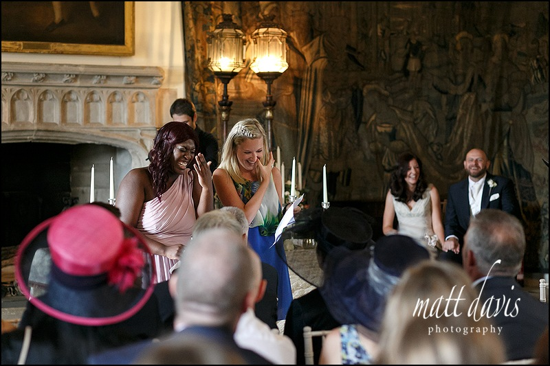 Wedding readings at Berkeley Castle wit guests laughing