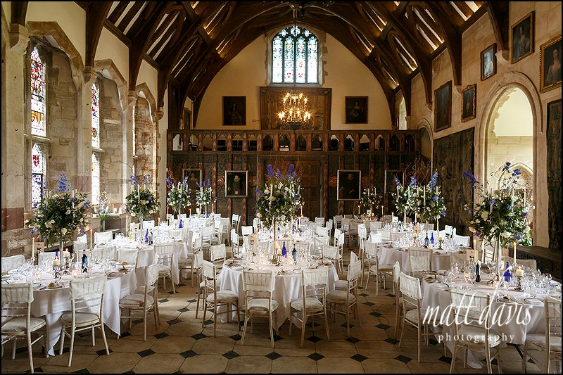 The great hall at Berkeley Castle packed with candle arbors and wedding flowers