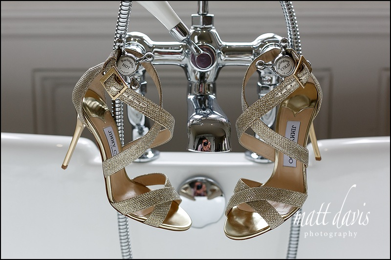 Jimmy Choo wedding shoes hung on a bath at Manor By The Lake, Gloucestershire
