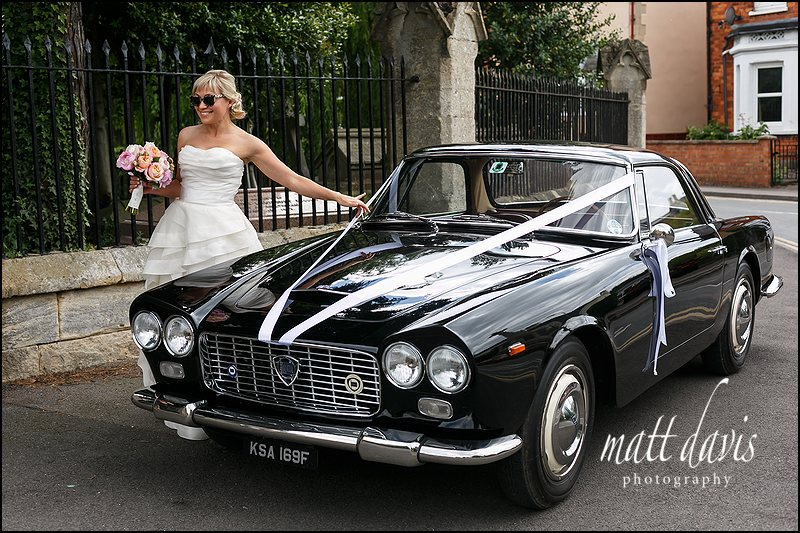 Rock 'n' Roll bride with vintage sports car on wedding day