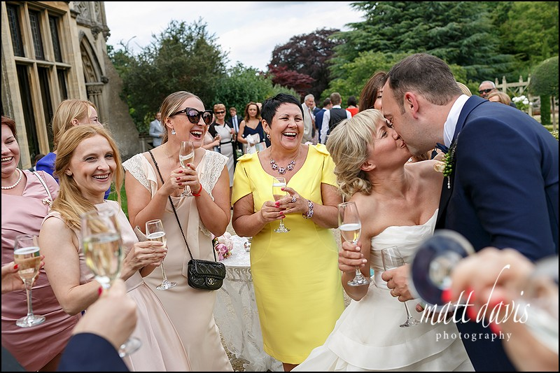 Wedding guests watch couple kiss at Manor By The Lake, Cheltenham