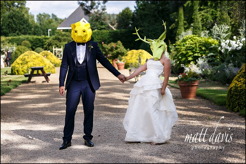 Quirky couple wear coloured animal masks at their Manor By The Lake wedding