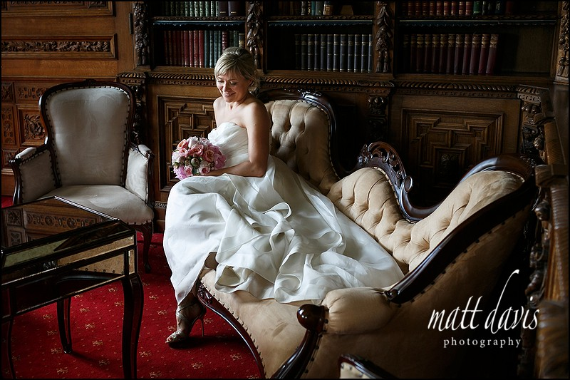 Bride poses on Chaise Lounge at manor By The Lake wedding