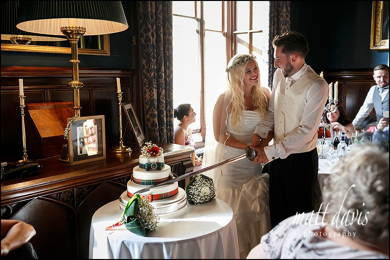 Wedding cake cutting with a sword at Eastnor Castle