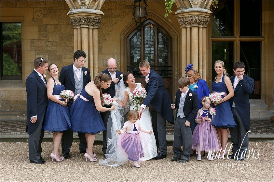 Documentary wedding group photo of brides veil being trodden on at Manor By The Lake.