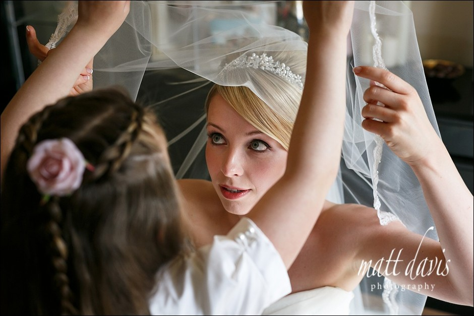 Wedding photography of bride with veil lifting over head.